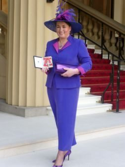 Alison Ward proudly shows her CBE outside Buckingham Palace